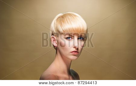 Close up Topless Attractive Young Woman with Short Blond Hair Looking at Camera Seriously on a Brown Background.