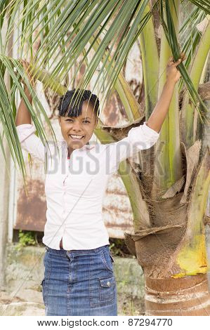 Laughing young woman stopped under coconut tree