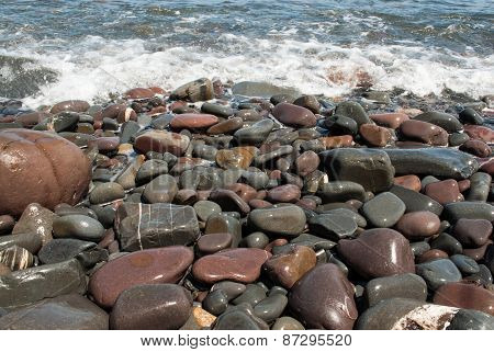 Pebbles on the Beach Being Washed by Wave