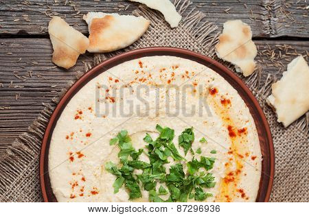 Plate of hummus, traditional lebanese food with pita, paprika and parsley