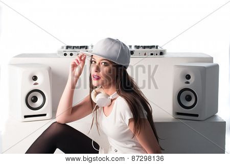 Trendy sexy young female DJ dressed in white mixing music at her deck and turntables looking up at the camera with a serious expression, isolated on white