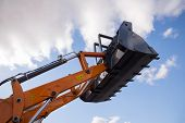 stock photo of excavator  - excavator arm with  basket against blue sky and clouds - JPG