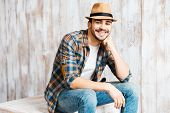 foto of fedora  - Handsome young man wearing hat and looking at camera while sitting against the wooden wall - JPG