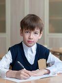 pic of diligent  - Diligent happy student sitting at desk classroom boy in school uniform - JPG