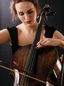 stock photo of cello  - Photo of a beautiful woman playing an old cello - JPG