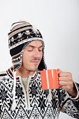 handsome winter man in sweater holding cup of hot tea