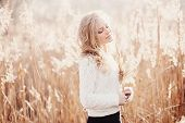 stock photo of pullovers  - Portrait of a beautiful young blonde girl in a field in white pullover smiling with eyes closed concept beauty and health - JPG