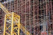 image of chute  - Construction background showing scaffolding on a construction site with a yellow trash chute running diagonally through the complexity - JPG