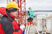 picture of theodolite  - surveyor working with theodolite transit equipment at construction site  - JPG