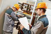 pic of fuse-box  - two electrician builder engineer works with electric cable wiring of fuse switch box - JPG