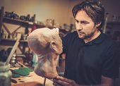 foto of prosthetics  - Man working in a prosthetic special fx workshop - JPG