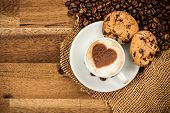 picture of mug shot  - Cup of coffee with heart shape on foam served in porcelain saucer on wooden table - JPG