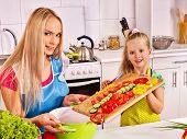 pic of pinafore  - Mother and daughter cooking food at kitchen - JPG
