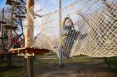 stock photo of crawling  - little boy crawling on suspension net bridge - JPG