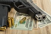 pic of corruption  - detail of gun with bullet on US dollar banknotes crime or corruption concept - JPG