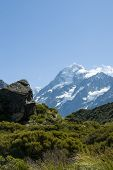 Постер, плакат: Mount Cook ahead beyond the lush green valley and rock outcrops