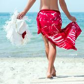 image of ankle shoes  - Beautiful woman with white hat walks at the sea side in red dress
