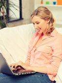 picture of telecommuting  - happy woman with laptop typing  at home - JPG