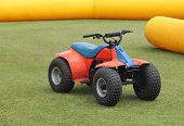 stock photo of dirt-bike  - A Mechanical Quad Bike on a Fun Day Circuit. ** Note: Soft Focus at 100%, best at smaller sizes - JPG