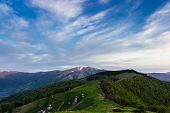 foto of pastures  - Landscape with mountain ranges forested slopes mountain pasture with buildings summer farm snowfields on top of the ridge and sky during sunrise - JPG