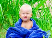 stock photo of naked children  - Little child sitting on the grass with blue towel - JPG