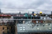 stock photo of partition  - Roofs and spiers of the city behind a glass partition in the rain - JPG