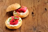 foto of scallion  - Two sandwiches with cured salmon cream cheese parsley capers and scallion on old wooden boards with space - JPG