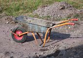 pic of wheelbarrow  - Muddy nice old construction site old wheelbarrow - JPG