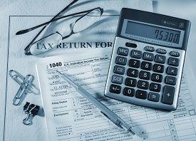 stock photo of calculator  - Tax accounting 1040 US Tax Form - JPG