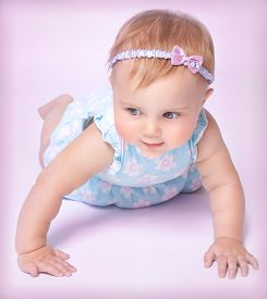 picture of little girls photo-models  - Cute little baby girl crawling in the studio on pink background - JPG