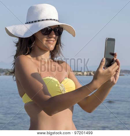 Young Woman On Beach Making Selfie