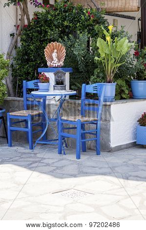 Traditional Blue Greek Chairs In A Backyard