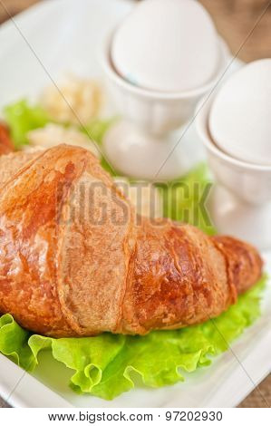 Tasty breakfast from eggs and croissant