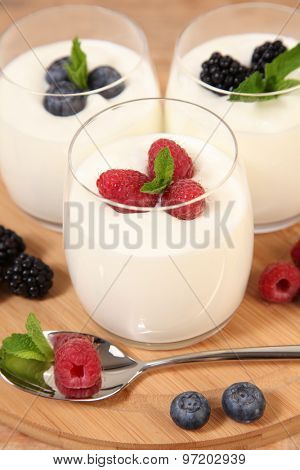 sweet berries with yogurt on wooden table