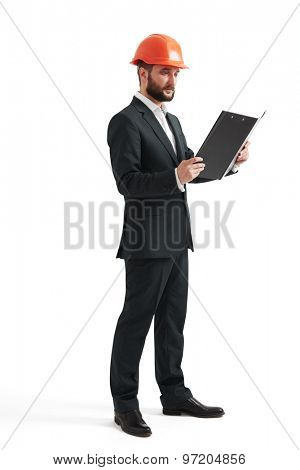 serious businessman in formal wear and orange helmet looking at black folder. isolated on white background