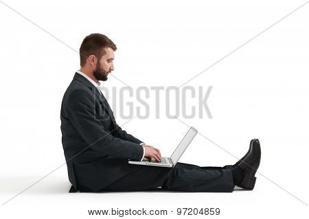 businessman in formal wear sitting on the floor and using laptop. isolated on white background
