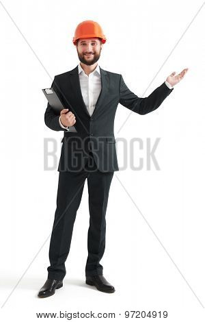 successful businessman in formal wear and orange helmet pointing his hand at something. isolated on white background