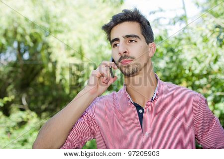 pensive young casual man on the phone, outdoor