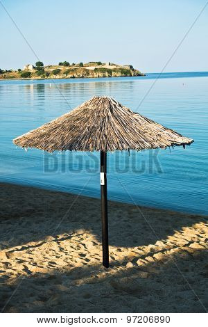 Thatched sunshade on a beach in front of old Roman fortress