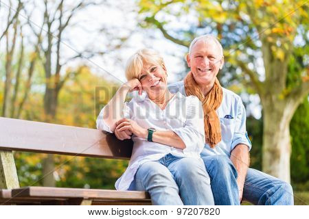 Senior woman and man sitting on part bench in fall