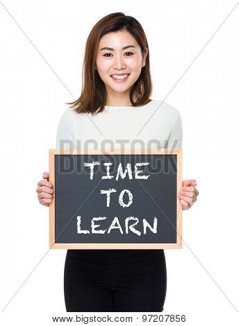 Young woman with the blackboard showing phrase of time to learn