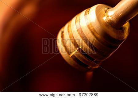 Wooden Dipper With Yellow Honey Flowing Over Dark Chocolate Colored Swirl Background Macro. Golden H