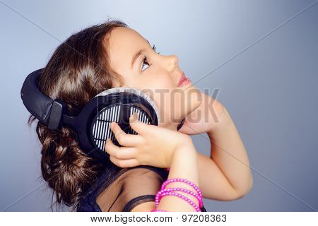 Funny cheerful girl listens to music on headphones. Childhood.