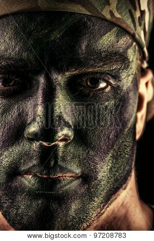 Close-up portrait of a brave soldier in war paint looking at camera. Black background. Military, war. Special forces.
