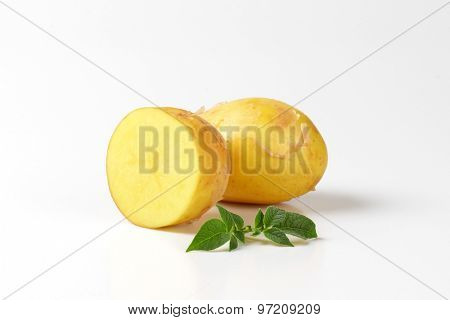 one and half baby potatoes with leaves on white background