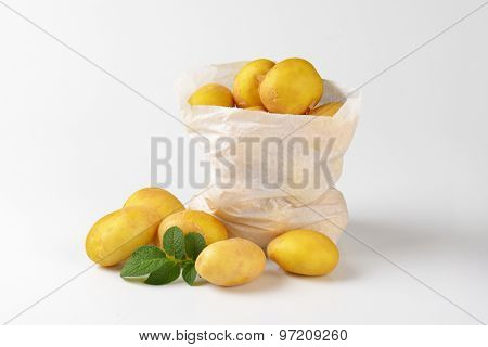 bag of fresh baby potatoes on white background