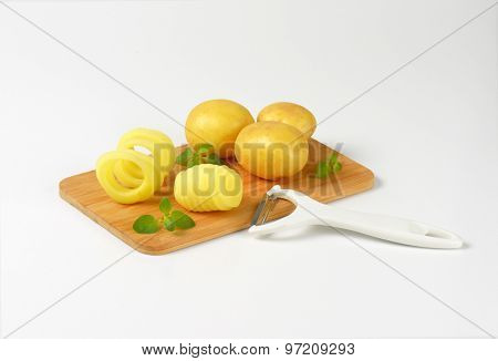 raw potatoes and peeler on wooden cutting board