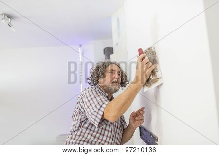 Middle-aged Male Builder Or Homeowner Plastering A White Wall Preparing It For Painting