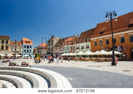 Brasov, Transylvania, Romania, 6th July 2015: Council Square is historical center of city, people walkinng and sitting at outdoor terraces and restaurants.
