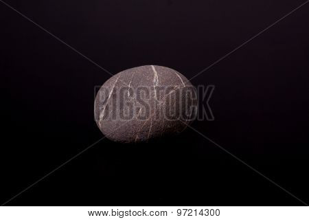 one pebble on black background
